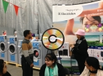 Norma Tidd oversees first spin of the prize wheel at the Ontario Laundry Systems show.