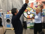 Marina Gibson, OLS President and CEO, oversees a spin at the prize wheel at recent Ontario Laundry Systems show.