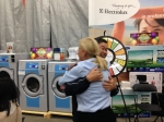 Marina Gibson and happy customer after spinning the prize wheel at Ontario Laundry Systems Show.