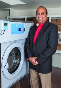 Raakesh Patel, owner of Super 8 in California, in his Electrolux-equipped laundry room with unique PLUS technology.